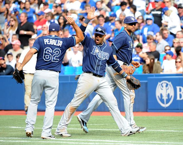 Tampa Bay Rays' Yunel Escobar, center, celebrates with teammates Joel Peralta and James Loney after turning a bases-loaded double play to end the seventh inning against the Toronto Blue Jays in a baseball game Sunday, Sept. 29, 2013, in Toronto. (AP Photo/The Canadian Press, Jon Blacker)