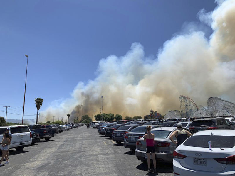 In this Sunday, June 9, 2019, photo provided by Joel Cannon, heavy smoke from a fast-moving brush fire surrounds Six Flags Magic Mountain and Hurricane Harbor, in Santa Clarita, Calif. (Joel Cannon via AP)