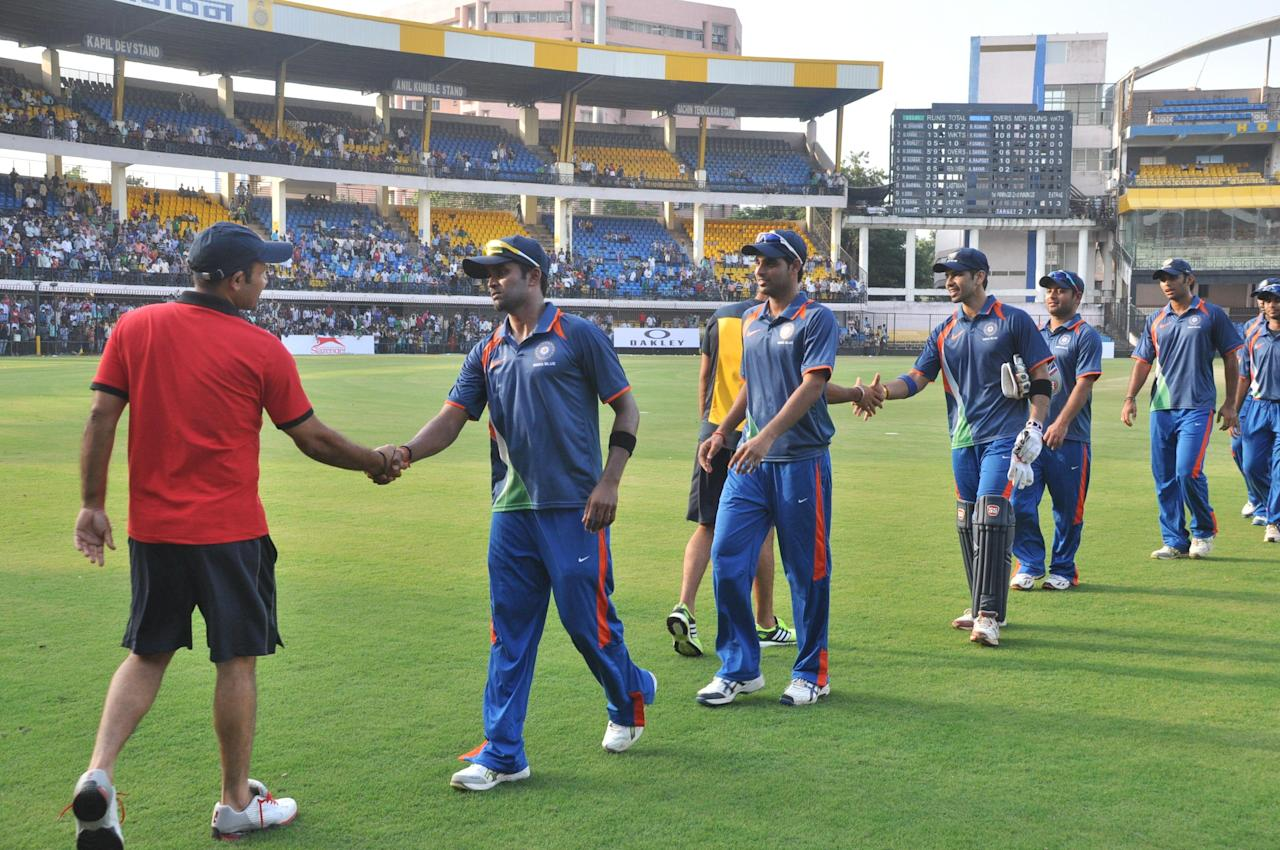 Virender Sehwag (Red) with R Vinay Kumar, Bhuvneshwar Kumar , N V Ojha, PP Chawla and A M Nayar during NKP Salve Challenger Trophy between India Blue and Delhi at Holkar Cricket Stadium in Indore on Sept. 26, 2013. (Photo: IANS)
