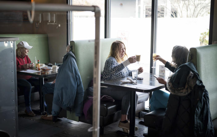 FILE - In this Jan. 11, 2021, file photo, Dawn Kaphingst, left, toasts to her cousin Jane Murray's birthday as the two cousins got together for the first time since the summer at Longfellow Grill, on the first day restaurants were allowed to reopen at 50 percent capacity, in Minneapolis. As the U.S. goes through the most lethal phase of the coronavirus outbreak yet, governors and local officials in hard-hit parts of the country are showing little willingness to impose any new restrictions on businesses to stop the spread. (Glen Stubbe/Star Tribune via AP, File)