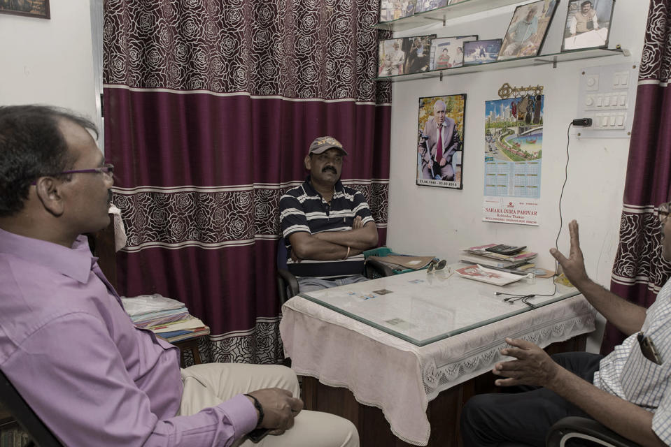 Bobby Gordon (43) in his office converses with the guardians of students who reside at the hostel he runs at his house. The hostel was started by his late father Noel Gordon, whose portrait hangs on the wall.