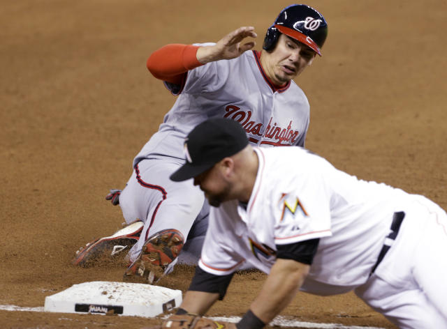 Washington Nationals' Jose Lobaton, left, is safe at third base on a throwing error by Miami Marlins catcher Jarrod Saltalamacchia during the sixth inning of a baseball game, Wednesday, April 16, 2014, in Miami. At right is Miami Marlins third baseman Casey McGehee. (AP Photo/Lynne Sladky)