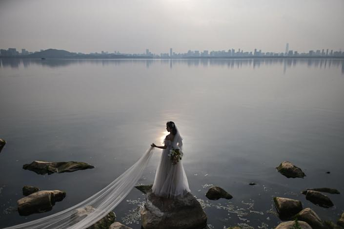 A bride poses for a wedding photograph next to East Lake in Wuhan, China.
