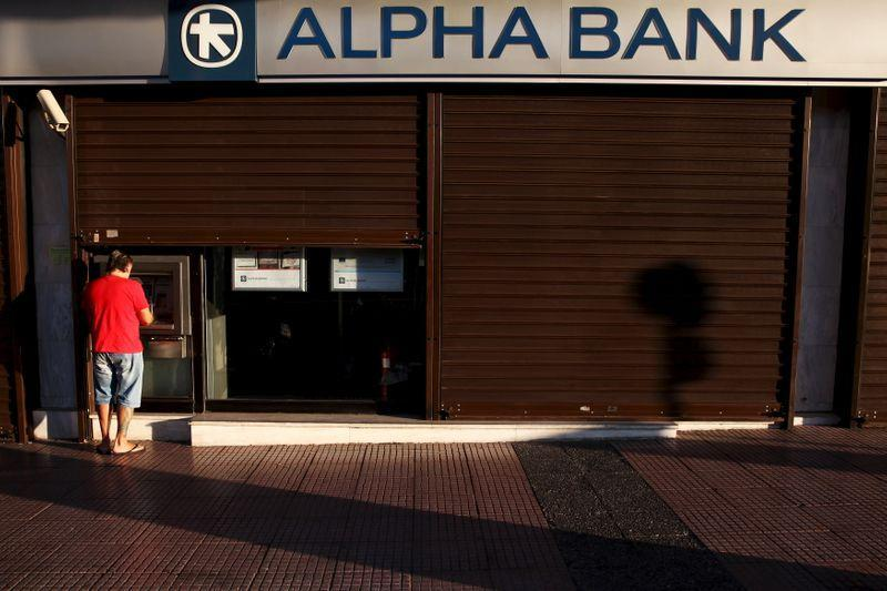 FILE PHOTO: A man withdraws money at an Alpha Bank branch ATM in central Athens