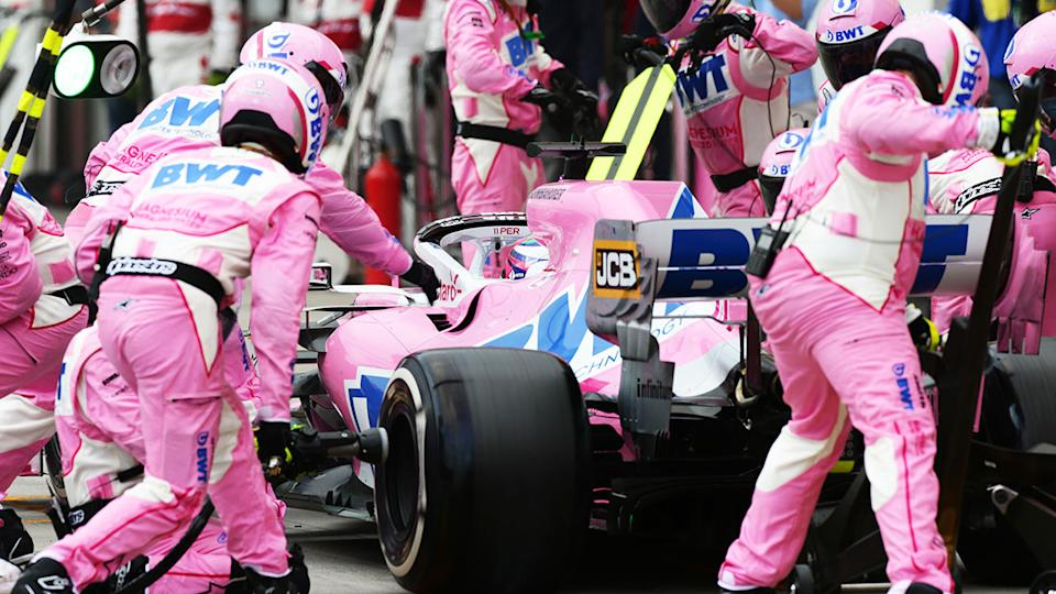 Racing Point's team can be seen working on one of the cars during an F1 race.