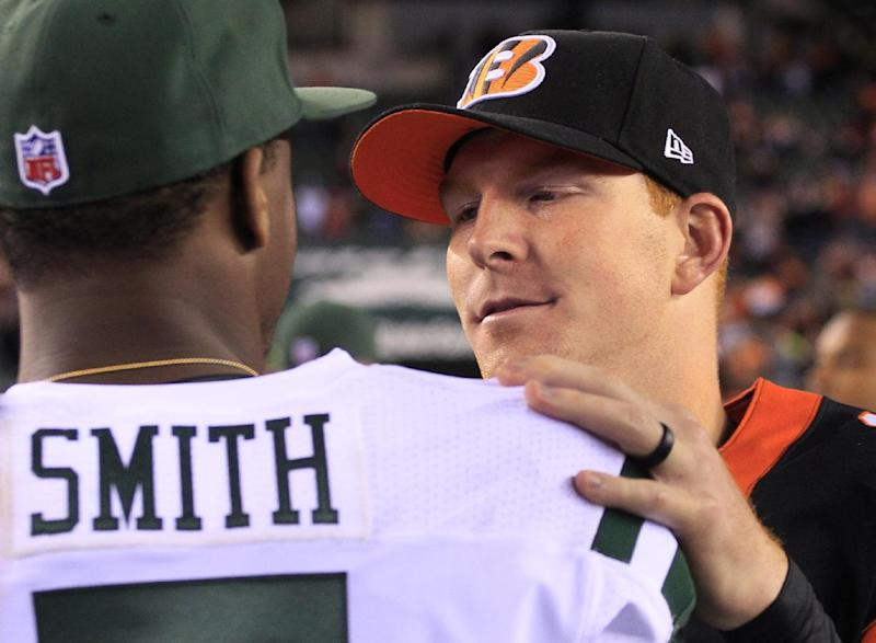 Cincinnati Bengals quarterback Andy Dalton, right, meets with New York Jets quarterback Geno Smith after the Bengals defeated the Jets 49-9 in an NFL football game, Sunday, Oct. 27, 2013, in Cincinnati. (AP Photo/Tom Uhlman)