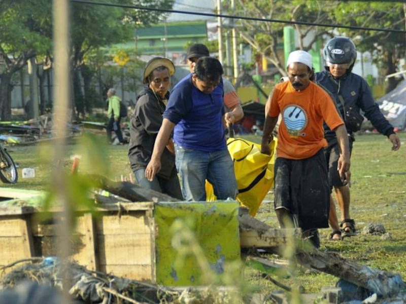 Residents carry a quake victim through Palu (AP)