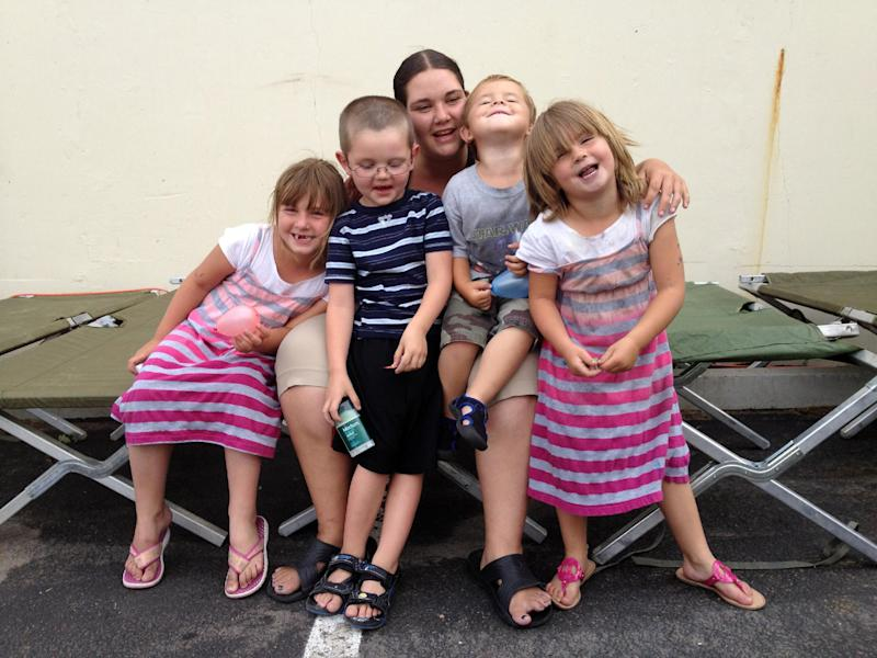 This June 27, 2012 photo shows Simone Covey, center, a 26-year-old single mother of three, sitting on a cot with her children and nephew at a Red Cross shelter in Colorado Springs, Colo., where they are staying after the Waldo Canyon Fire forced them from their home. Covey doesn't know if the apartment was damaged by the fire, which has destroyed hundreds of homes and has so far forced mandatory evacuations for more than 32,000 residents. Pictured from left to right are Emma Covey, 6; Covey's nephew, Zack Miller, 5; Simone Covey; Logan Thompson-Covey, 2 and Nyomie Covey, 5. (AP Photo/Thomas Peipert)