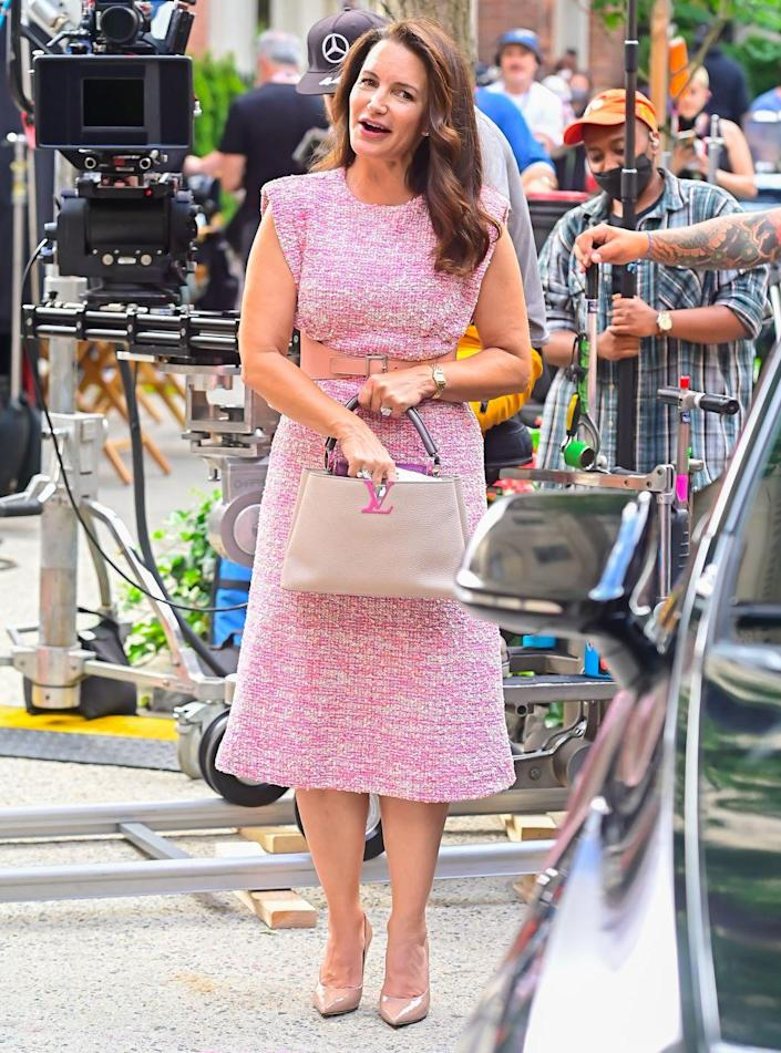 <p>In a classicly elegant, conservative Charlotte York-Goldenblatt look, Kristin Davis wore a St. John tweed empire-waist midi dress and Jimmy Choo Love 100 ballet-pink patent-leather pointed pumps, accessorized with Cartier's Panthère de Cartier watch and a Louis Vuitton Capucines bag. She wore her hair in elegant loose waves. <br></p>