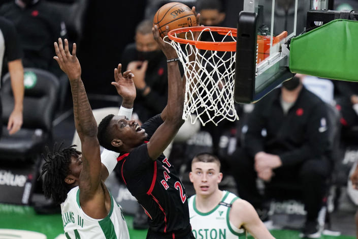 Toronto Raptors guard Terence Davis (0) shoots after grabbing a rebound against Boston Celtics center Robert Williams III, left, during the first half of an NBA basketball game, Thursday, March 4, 2021, in Boston. At right is Boston Celtics guard Payton Pritchard. (AP Photo/Charles Krupa)