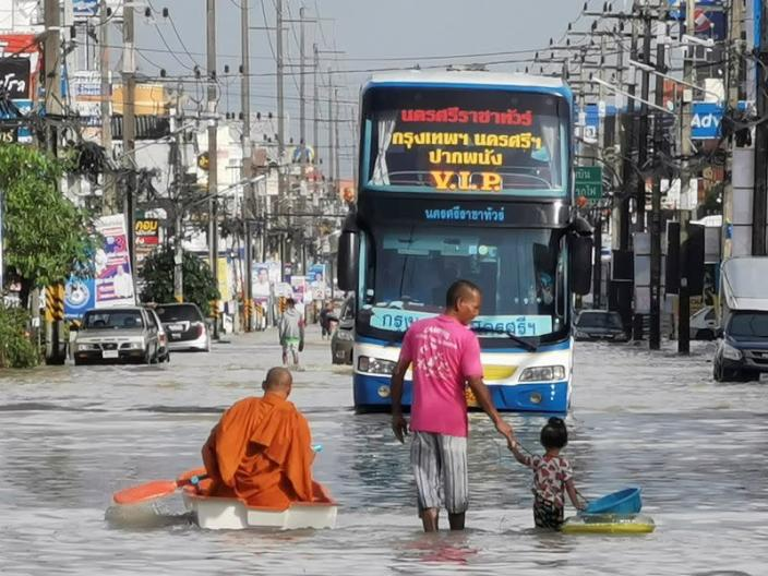Buddhist monk paddles a boat down a flooded street in Nakon Si Thammarat province