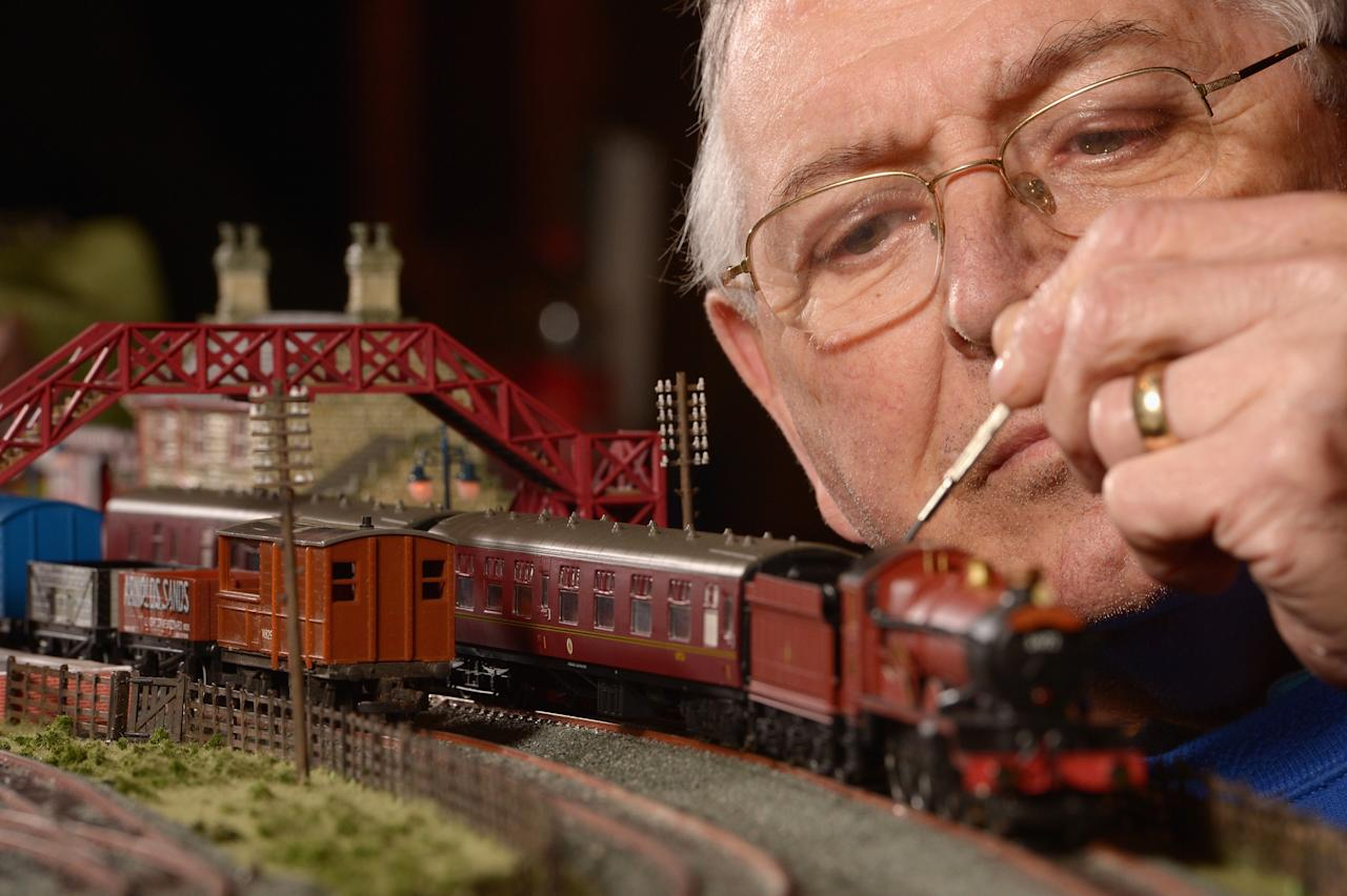 GLASGOW, SCOTLAND - FEBRUARY 21: Dave Patterson tinkers with a model train as enthusiasts gather for the Model Rail Scotland exhibition on February 21, 2013 in Glasgow, Scotland. Model railway clubs from all corners of the UK and parts of Europe will be displaying over 50 model railway layouts at this year's event held at The Scottish Exhibition Centre in Glasgow from February 22nd to the 24th. (Photo by Jeff J Mitchell/Getty Images)