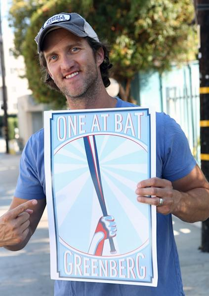 "In a Sept. 4, 2012, photo provided by Triple Threat TV, Matt Liston gesturing toward a poster in Los Angeles. Liston, a filmmaker and Chicago Cubs fan, was watching the night Adam Greenberg got beaned in his first - and only - at-bat in the majors. He never forgot about it, either. He'd already made a film about the Cubs' 2003 season called ""Chasing October"" and he's contemplating another about that night. But his first order of business was to get Greenberg back into the box in a real game. That's how the ""One At Bat"" campaign came about. A petition on Change.org asking one of MLB's clubs to give him the chance before the end of this season has already collected nearly 15,000 signatures. (AP Photo/Triple Threat TV, Jeven Dovey)"