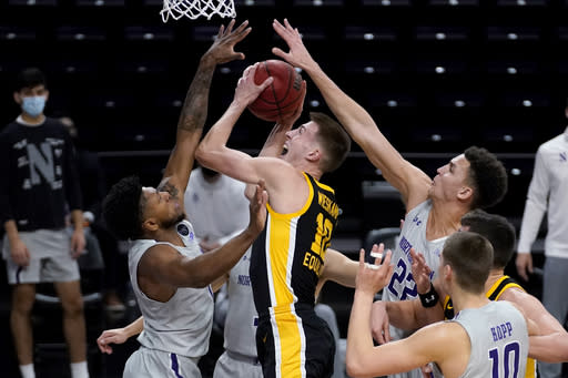 Iowa guard/forward Joe Wieskamp, center, goes up for a shot between Northwestern guard Anthony Gaines, left, and forward Pete Nance during the first half of an NCAA college basketball game in Evanston, Ill., Sunday, Jan. 17, 2021. (AP Photo/Nam Y. Huh)