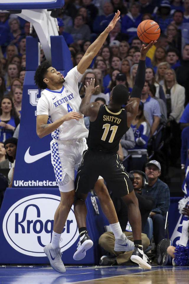 Vanderbilt's Simisola Shittu (11) shoots under pressure from Kentucky's Nick Richards (4) during the first half of an NCAA college basketball game in Lexington, Ky., Saturday, Jan. 12, 2019. (AP Photo/James Crisp)