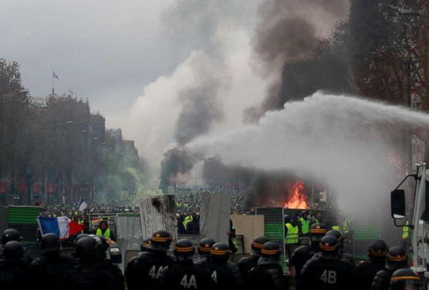 PHOTO: Protesters wearing yellow vests, a symbol of a French drivers' protest against higher fuel prices, run from police during riots on the Champs-Elysees in Paris, Nov. 24, 2018. (Gonzalo Fuentes/Reuters)