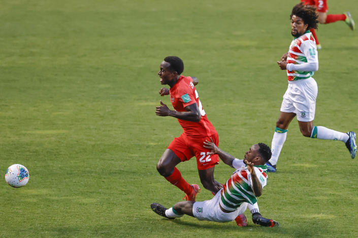Suriname's Ridgeciano Haps (5) fouls Canada's Richie Laryea (22) during the first half of a World Cup 2022 Group B qualifying soccer match Tuesday, June 8, 2021, in Bridgeview, Ill. (AP Photo/Kamil Krzaczynski)