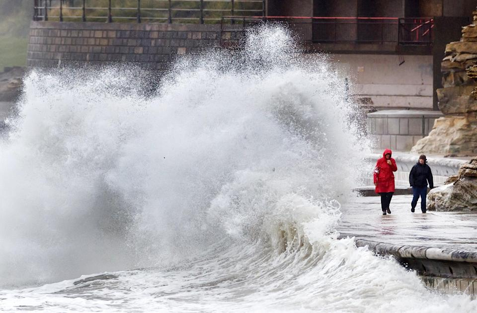 People walk along the windy seafront in Scarborough (PA Archive)