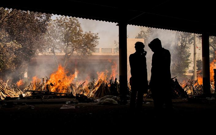People are silhouetted against multiple burning funeral pyres of patients who died of the Covid-19 coronavirus disease at a crematorium on April 24, 2021 in New Delhi, India - Anindito Mukherjee/Getty Images