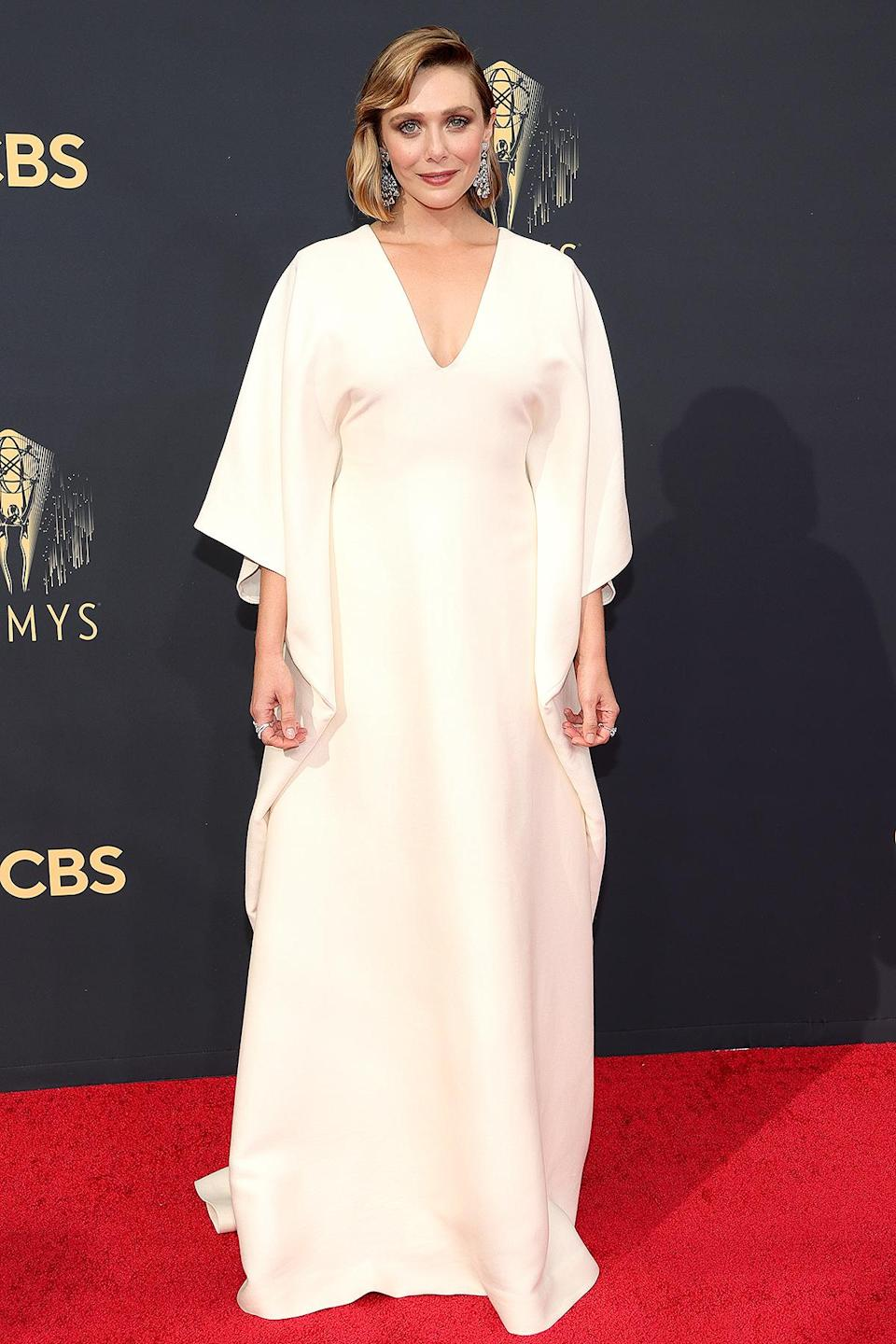 <p>in a cream-colored V-neck gown with draped sleeves by The Row (designed by her sisters Mary-Kate and Ashley Olsen) with Chopard chandelier earrings and rings. </p>