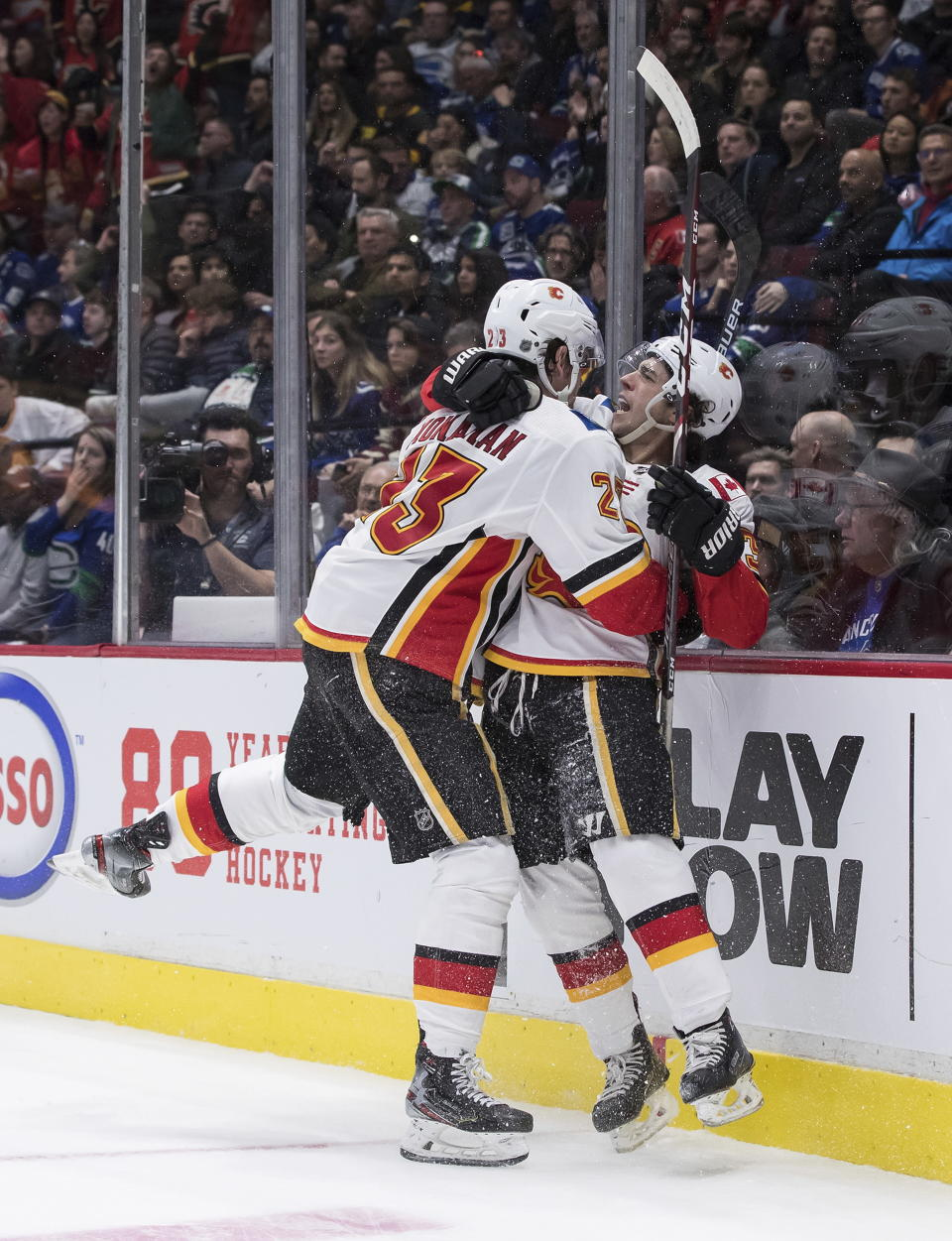 Calgary Flames' Johnny Gaudreau, right, and Sean Monahan celebrate Monahan's goal against the Vancouver Canucks during the third period of an NHL hockey game Saturday, Feb. 8, 2020, in Vancouver, British Columbia. (Darryl Dyck/The Canadian Press via AP)