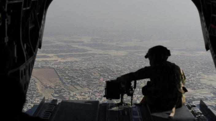 US soldier sits in the rear of Chinook helicopter while flying over Kabul on 10 August 2017
