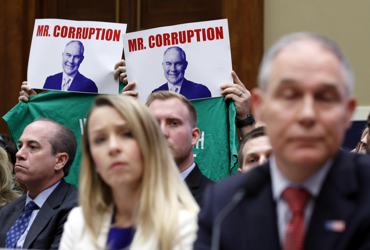 Protestors hold up signs and message T-shirts behind EPA chief Scott Pruitt, and Holly Greaves, EPA chief financial officer, as they testify at a hearing of the House Energy and Commerce subcommittee. (AP Photo/Alex Brandon)