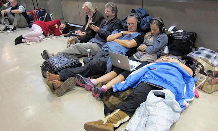 Passengers sit and sleep on the floor as they wait for flights, many of which were delayed or canceled due to heavy snowfall, at Narita International Airport, outside of Tokyo, Tuesday, Jan 15, 2013. This winter's first snow in the Tokyo area severely disrupted travel. (AP Photo Nick Ut)
