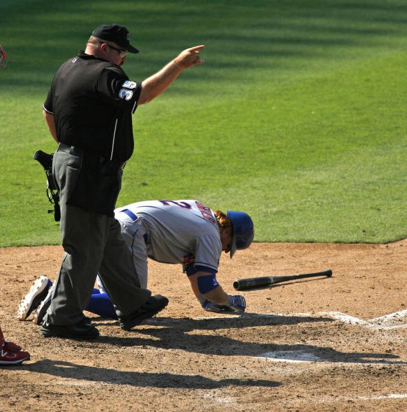 Home plate umpire Wally Bell singles to first after New York Mets' Justin Turner was hit by a pitch in the ninth inning of a baseball game against the Philadelphia Phillies, Thursday, Aug. 30, 2012, in Philadelphia. The Phillies won 3-2. (AP Photo/H. Rumph Jr)
