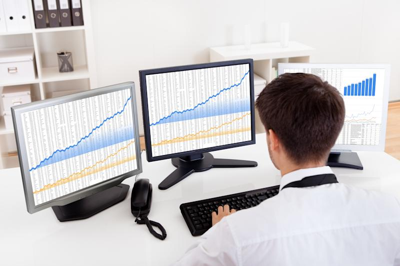 A man using a computer with three different monitors full of charts and graphs.