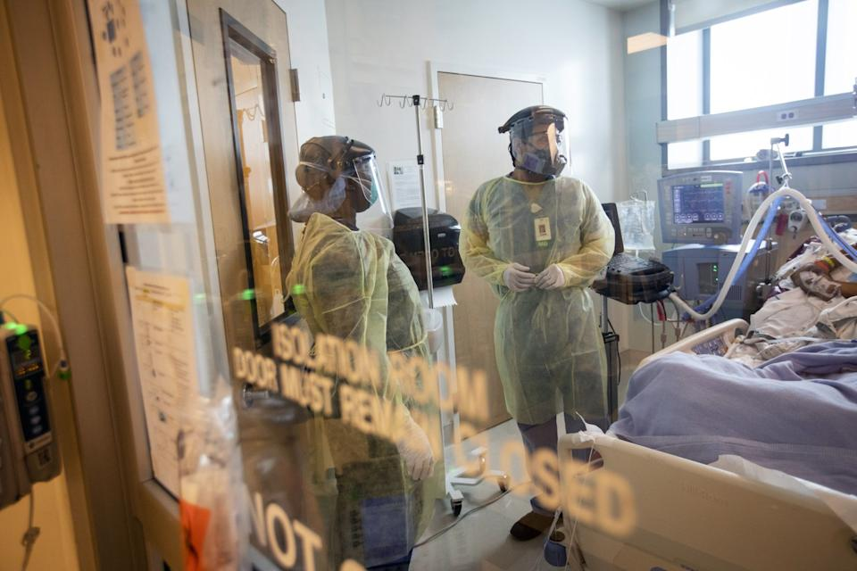 Two health workers in full protective gear observe a patient in an isolation room.