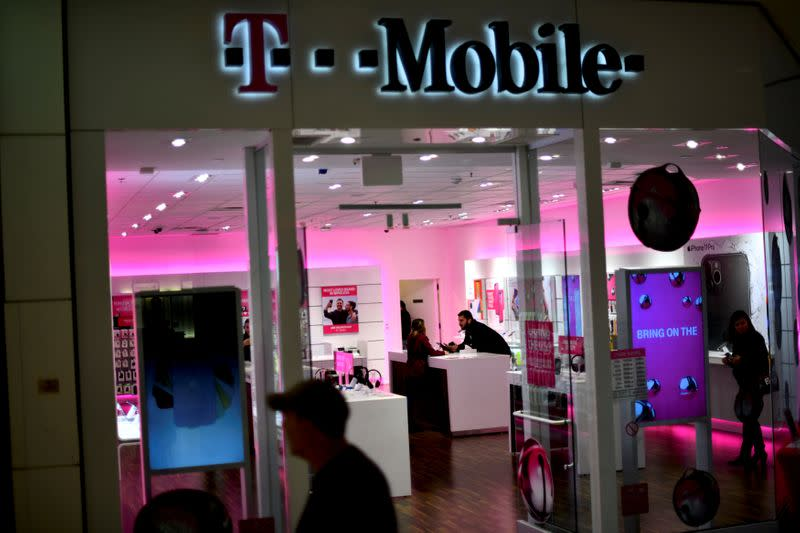FILE PHOTO: A T-Mobile employee assists a customer as holiday shopping accelerates at the King of Prussia Mall