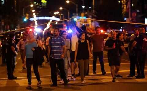 People leave an area taped off by the police near the scene of a mass shooting in Toronto - Credit: CHRIS HELGREN /Reuters