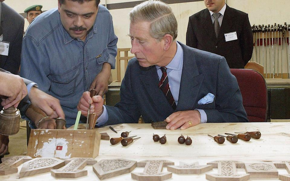 The Prince of Wales tries his hand at wood carving during his visit to a workshop of Islamic Arts at Al-Balqa University  - Getty Images