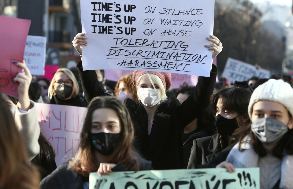 Young people wearing face masks carry banners during a protest march through downtown Skopje, North Macedonia, on Wednesday, Feb. 3, 2021. Several hundred mostly young people have gathered in front of the North Macedonia's Interior ministry on Wednesday to protest sexual harassment of women on social media and policy of impunity for that kind of violence. (AP Photo/Boris Grdanoski)