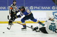 St. Louis Blues' Ryan O'Reilly (90) passes around San Jose Sharks' Brent Burns (88) during the second period of an NHL hockey game Monday, Jan. 18, 2021, in St. Louis. (AP Photo/Jeff Roberson)