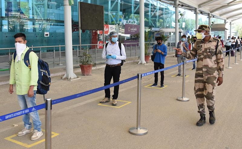 Travellers stand while maintaining social distancing before entering Sri Guru Ramdas Jee International Airport on May 25, 2020 in Amritsar, India. Domestic flight operations resumed on Monday after a gap of two months owing to the lockdown against coronavirus. (Photo by Sameer Sehgal/Hindustan Times via Getty Images)