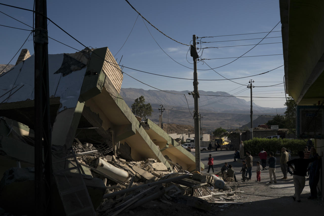 <p>People walk next to a destroyed house after an earthquake in the city of Darbandikhan, northern Iraq, Monday, Nov. 13, 2017. (Photo: Felipe Dana/AP) </p>