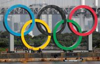 Workers prepare to carry the giant Olympic rings, which are being temporarily removed for maintenance, at the waterfront area at Odaiba Marine Park in Tokyo