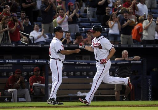 Atlanta Braves' Chipper Jones, right, is congratulated by coach Brian Snitker while rounding third base after hitting a two-run home run against the Arizona Diamondbacks during the sixth inning of a baseball game on Wednesday, June 27, 2012, in Atlanta. (AP Photo/John Amis)