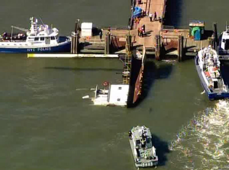 In this image provided by WABC-TV an overturned tug boat, center, sits in the water near Liberty Island in New York on Friday, April 6, 2012. Three crew members were rescued after the boat tipped over while trying to lift something with a crane on the vessel. (AP Photo/WABC-TV)