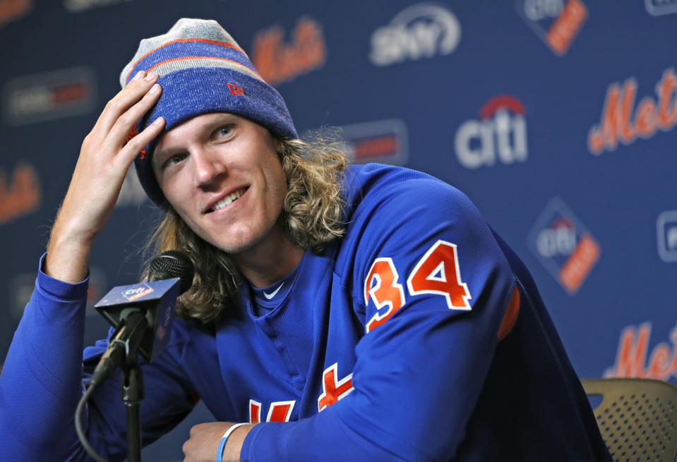 New York Mets opening day pitcher Noah Syndergaard smiles as he describes the Mets new manager Mickey Callaway and realizes Callaway is in the room listening to his description during a news conference following a pre-opening day workout at Citi Field, Wednesday, March 28, 2018, in New York. (AP Photo/Kathy Willens)