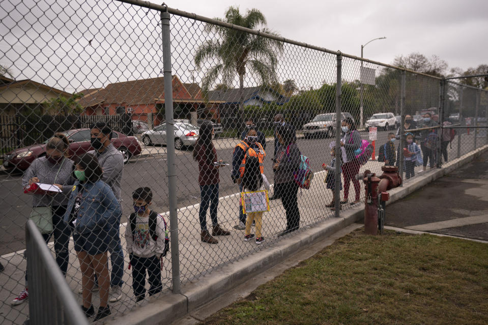 Parents and students wait in line to check in on the first day of in-person learning at Heliotrope Avenue Elementary School in Maywood, Calif., Tuesday, April 13, 2021. More than a year after the pandemic forced all of California's schools to close classroom doors, some of the state's largest school districts are slowly beginning to reopen this week for in-person instruction. (AP Photo/Jae C. Hong)