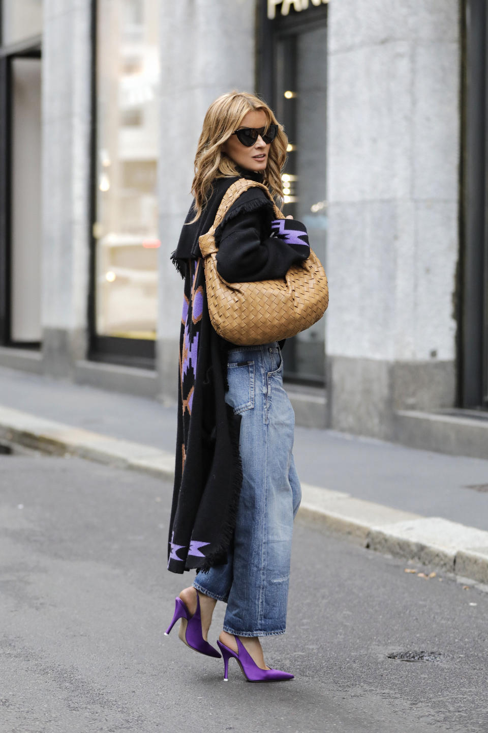MILAN, ITALY - SEPTEMBER 25: Influencer Gitta Banko, wearing light blue baggy denim jeans by Saint Laurent, a black cashmere turtleneck sweater by Boscana, a black oversized knit coat with purple pattern on the back and cuffs by Antonia Zander, purple pumps by The Attico, sunglasses by Bottega Veneta and a camel colored Jodie bag by Bottega Veneta, is seen during the Milan Women's Fashion Week on September 25, 2020 in Milan, Italy. (Photo by Streetstyleshooters/Getty Images)