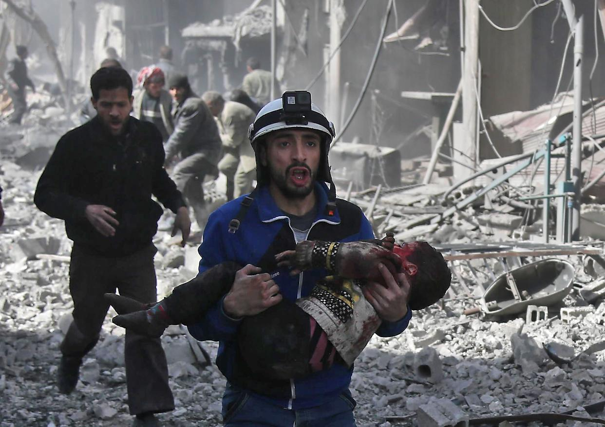 A Syrian civil defense member carries an injured childafter agovernment bombing in the rebel-held town of Hamouria in Syria's besieged eastern Ghouta region. (Photo: ABDULMONAM EASSA via Getty Images)