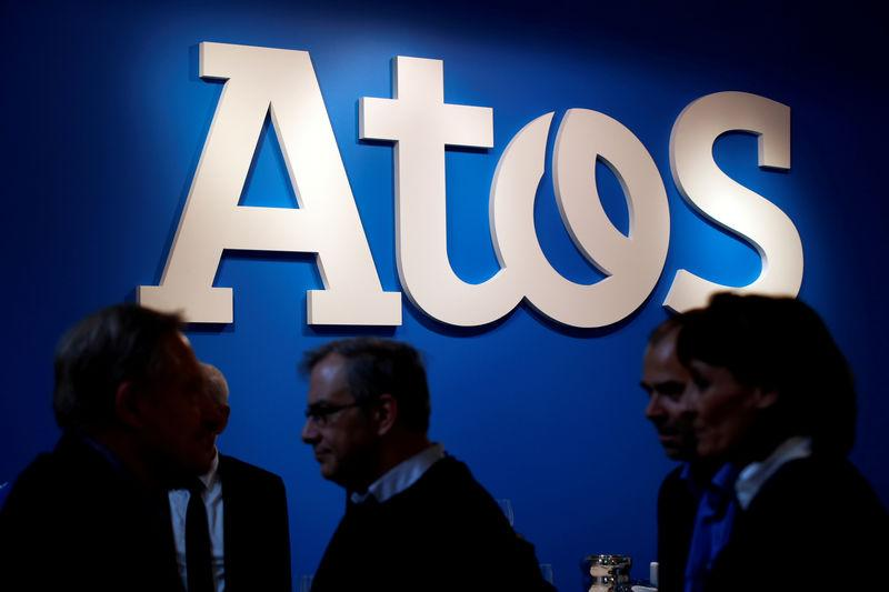 FILE PHOTO: People walk in front of the Atos company's logo during a presentation of the new Bull sequana supercomputer in Paris