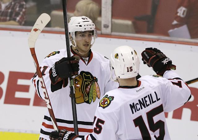 Chicago Blackhawks left wing Garret Ross (61) is congratulated by teammate Mark McNeill after scoring during the third period of an NHL hockey game against the Detroit Red Wings in Detroit, Thursday, Sept. 25, 2014. (AP Photo/Carlos Osorio)