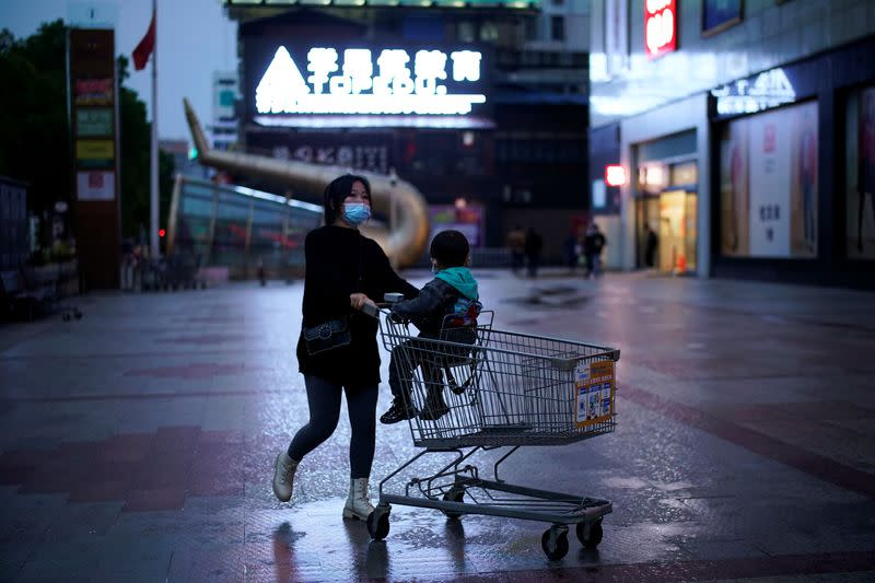 Woman wearing a face mask pushes a shopping trolley with a child sitting on it outside a shopping mall in Xianning
