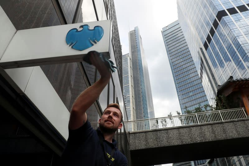 FILE PHOTO: A worker cleans a Barclays logo outside a bank branch in the financial district of London