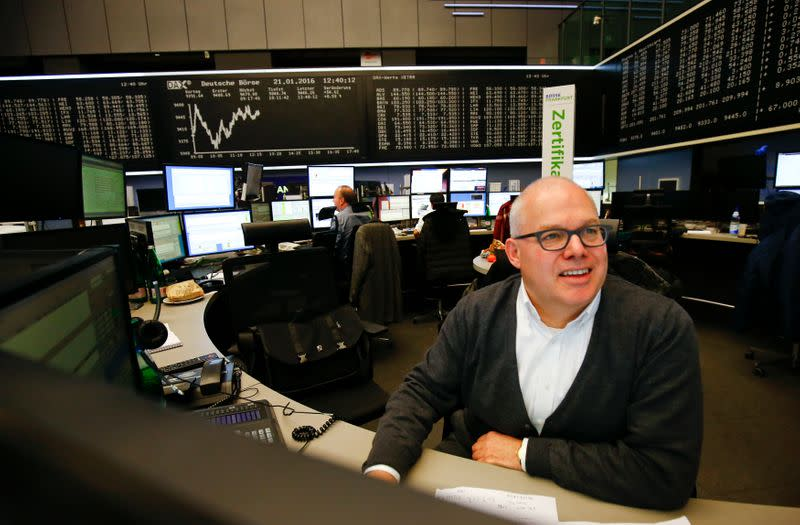 A trader works at his desk in front of the German share price index, DAX board, at the stock exchange in Frankfurt